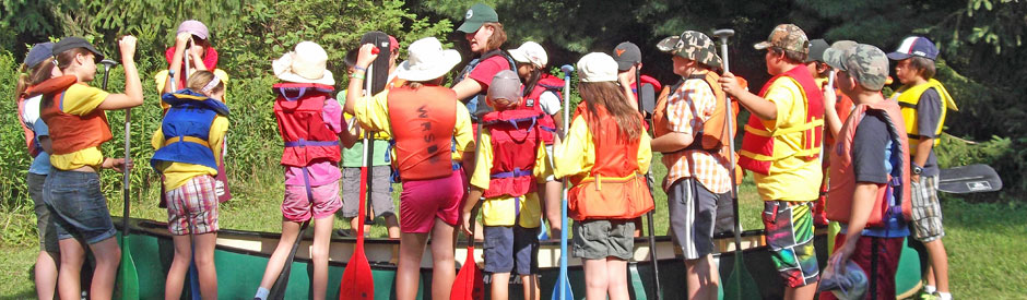 School glass in life vests taking in a canoeing lesson