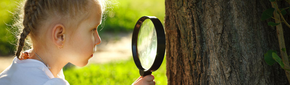 Girl looking at tree with magnifying glass