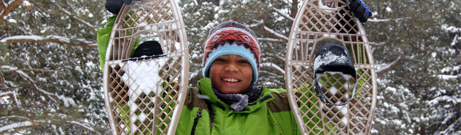 Smiling boy holding snowshoes