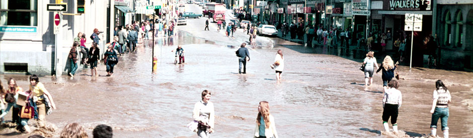 Flood of 1974, downtown Galt (cambridge) with crowd of people in street