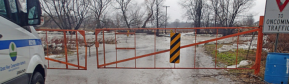 Flooded road with emergency gates across it, closing it