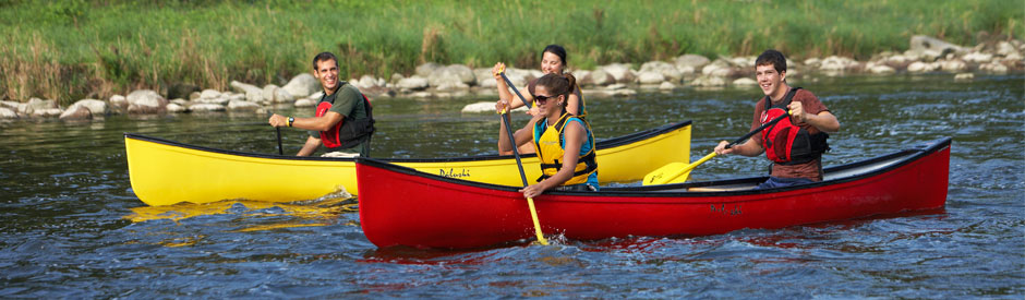 Smiling young people paddling the Grand River