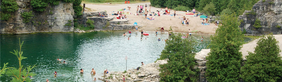 People enjoying the beach and blue waters of Elora Quarry Park