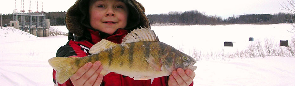 Boy holding a fish with Shand Dam in background, in winter