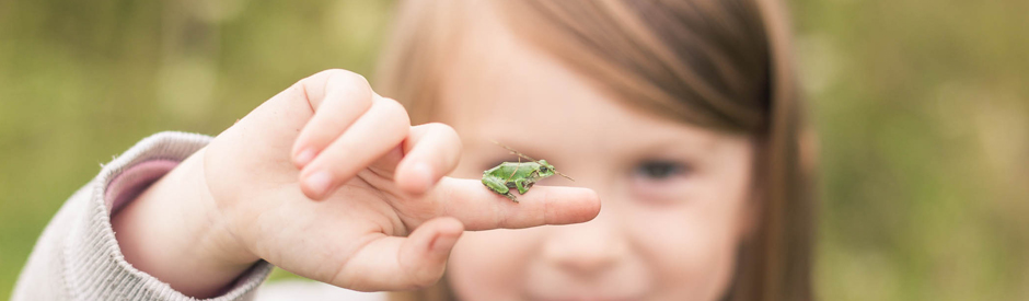 Girl holding frog on her finger