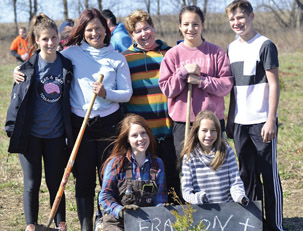 Susan Frasson and family standing behind a sign while planting trees in Guelph